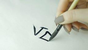 Kobiety ` s wręcza writing chińczyka hieroglif Żeńska ręka trzyma writing muśnięcia kaligrafii Chińskich charaktery, zamyka up Zdjęcie Royalty Free