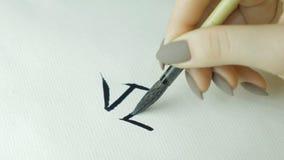 Kobiety ` s wręcza writing chińczyka hieroglif Żeńska ręka trzyma writing muśnięcia kaligrafii Chińskich charaktery, zamyka up Fotografia Stock