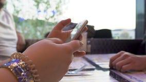 Kobiety scrolling środków ogólnospołeczne strony na smartphone, spotkanie przyjaciele w kawiarni zbiory