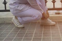 Kobiety siedzą wiązanych sneakers Zdjęcie Royalty Free