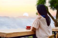 Kobiety siedzi pijący kawową dopatrywanie mgłę, ranek i zdjęcia stock