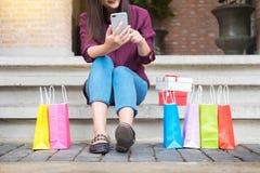 Kobiety spojrzenie przy telefonem komórkowym z paperbags w centrum handlowym podczas gdy enjo fotografia stock
