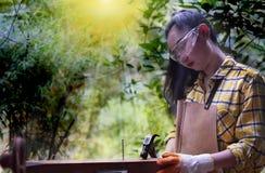 Kobiety stoi budowniczego jest ubranym sprawdzać koszulowego pracownika młotkuje gwóźdź w drewnianym budowa fotografia royalty free