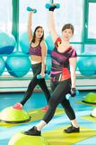Kobiety stoi na równowagi deskowym robi ćwiczeniu z dumbbells Zdjęcia Royalty Free