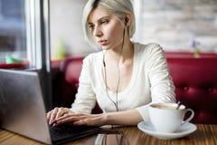 Kobiety Słuchająca muzyka Podczas gdy Pracujący Na laptopie W kawiarni Zdjęcia Stock
