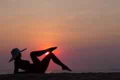 Kobiety sylwetka z kapeluszowym lying on the beach na dennym tle Fotografia Royalty Free