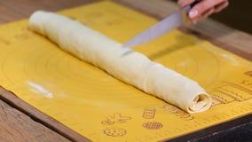 Kobiety tnący ciasto dla cynamonowych rolek na stole, zbliżenie zdjęcie wideo