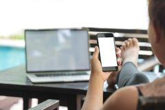 Kobiety trzyma telefonu bielu ekranu obsiadanie relaksują plenerowego l Obraz Stock