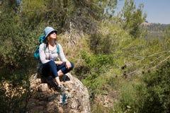Kobiety turystyczny backpacker siedzi odpoczynkowego kamiennego wycieczkuje lasu krajobraz Fotografia Stock
