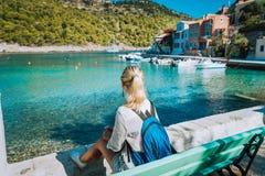 Kobiety turystyczny obsiadanie na banku przed piękną morze zatoką na lato ranku Uroczy wakacje w Assos wiosce z zdjęcia royalty free