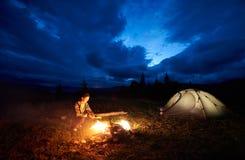 Kobiety turystyczny odpoczywać przy noc campingiem w górach zbliża ognisko i namiot pod evening chmurnego niebo zdjęcia royalty free