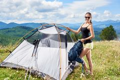 Kobiety turystyczny wycieczkować w halnym śladzie, cieszy się lato pogodnego ranek w górach zbliża namiot fotografia royalty free