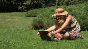 Kobiety uściśnięcia laptop Żeńskiego flirtu online obsiadanie na parkowym gazonie w pogodnym letnim dniu 4K zbiory wideo