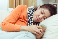 Kobiety używa telefon komórkowego w domu z czytelniczą wiadomością Obraz Royalty Free
