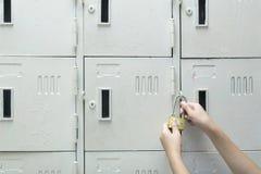 Kobiety używają kędziorek kłódki szafki zdjęcia royalty free