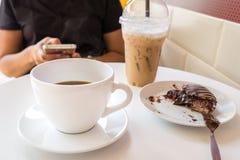 Kobiety używa smartphone w kawowej restauraci Obraz Royalty Free