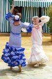 Kobiety ubierali w colourful flamenco sukniach, tanu przy Seville Kwiecień jarmarkiem i Obraz Stock