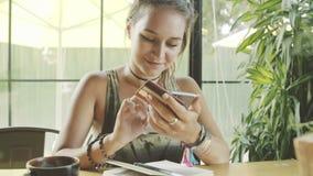 Kobiety use online bankowość z smartphone w kawiarni zbiory wideo