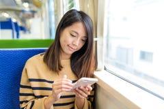 Kobiety use telefon komórkowy na pociągu Zdjęcia Stock