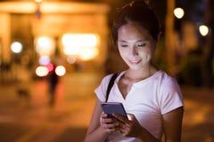 Kobiety use telefon komórkowy przy nocą w mieście Obraz Stock