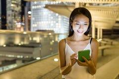 Kobiety use telefon komórkowy w mieście przy nocą Obrazy Stock