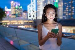 Kobiety use telefon komórkowy w mieście przy nocą Zdjęcie Stock
