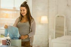 Kobiety w ciąży mienia dzieci odziewają dla przyszłościowego dziecka obraz stock