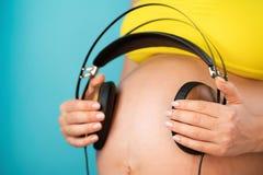 Kobiety w ciąży mienia słuchawki na jej brzuchu z dzieckiem, cieszy się ulubioną muzykę na błękitnym tle maternity obraz stock