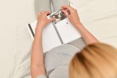 Kobiety w ciąży mienia ultradźwięku wizerunek i robi notatkom w notatniku Oczekiwanie dziecko zdjęcie royalty free