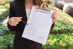 Kobiety w kostiumu pokazuje ubezpieczenie samochodu polisę i wskazuje z p Zdjęcia Royalty Free