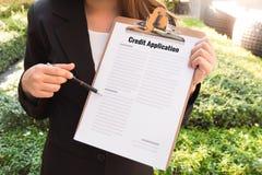 Kobiety w kostiumu pokazuje zatwierdzonego kredytowego zastosowanie i wskazuje w zdjęcie stock