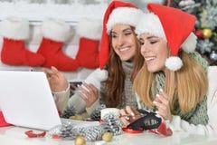 Kobiety w Santa kapeluszach używać laptop Fotografia Stock