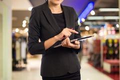 Kobiety w zakupy centrum handlowym używać mobilnego pastylka peceta Fotografia Royalty Free