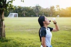 Kobiety woda pitna ćwiczy przy ogródem w zmierzchu po tym jak działający Obrazy Stock