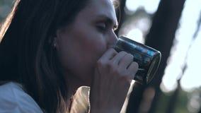 Kobiety woda pitna od żelaznego kubka w lesie na tle słońca świecenie zbiory