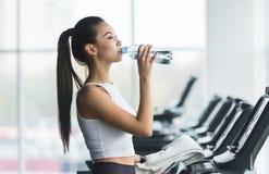Kobiety woda pitna po ćwiczyć na karuzeli zdjęcie royalty free