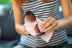Kobiety wręczają czyści ochronnych okulary przeciwsłonecznych z mikro włókna wytarciem obrazy royalty free