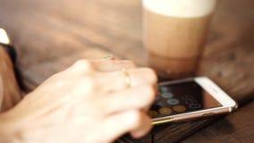 Kobiety wręczają używać smartphone dla kalkulatora przy kawową kawiarnią zbiory wideo