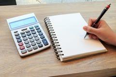 Kobiety wręczają writing z ołówkiem, notatnikiem i kalkulatorem, Zdjęcia Royalty Free