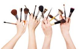 Kobiety wręczają z kosmetycznymi muśnięciami dla makeup na bielu zdjęcia stock