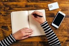 Kobiety writing kontaktu lista od telefonu w biznesową agendę Zdjęcie Royalty Free
