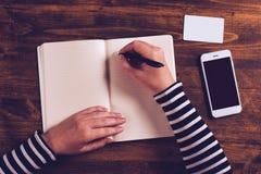 Kobiety writing kontaktu lista od telefonu w biznesową agendę Obrazy Stock