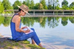 Kobiety writing przy nadbrzeżnym w naturze Obrazy Royalty Free