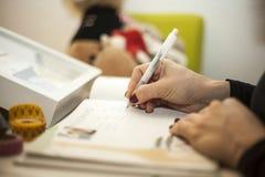 Kobiety writing w dziecko książce Obrazy Royalty Free