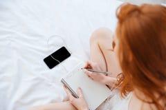 Kobiety writing w dzienniczku i słuchanie muzyka od smartphone fotografia royalty free