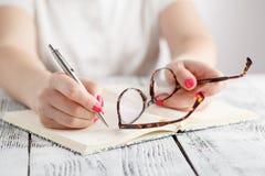Kobiety writing w notepad umieszczającym na jaskrawym desktop Edukacja przeciw zdjęcie stock