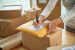 Kobiety writing wysyłki adres zdjęcia royalty free