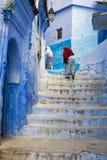 Kobiety wspina się schodek w miasteczku Chefchaouen w Maroko Zdjęcie Stock