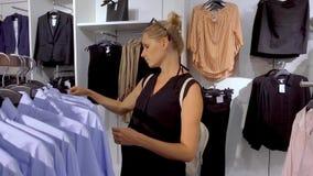 Kobiety wybierać nowy odziewa w sklepie odzieżowym zdjęcie wideo