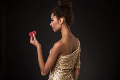 Kobiety wygranie - młoda kobieta trzyma dwa czerwonego układu scalonego w z klasą złoto sukni, grzebak as grępluje kombinację Zdjęcia Royalty Free